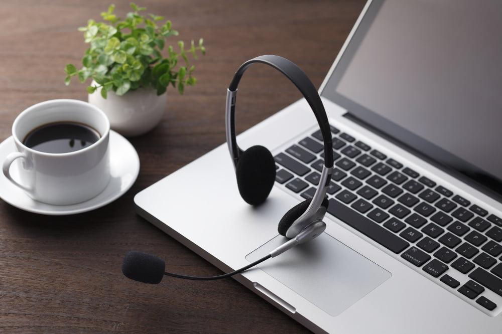 Komunikatory do zastosowania w firmie. Słuchawki do rozmowy położone na komputerze.